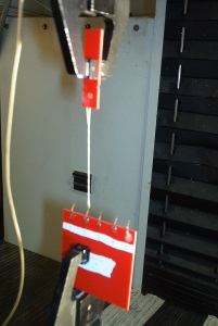 Figure 3 - Hook Testing in the Instron Tensile tester.  Arrow indicates looped thread.